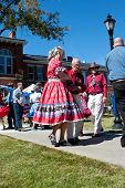Senior Citizen Couple Square Dances At Outdoor Event