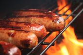 stock photo of grilled sausage  - brats cooking on the grill  - JPG