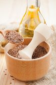 picture of flax seed oil  - mortar with flax seeds and linseed oil in glass jug - JPG