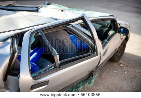 Close up side view of a silver motor car crumpled and destroyed in an accident with its windows blown out and shattered and roof caved in