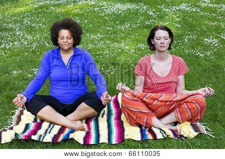Two Women Meditating In Park