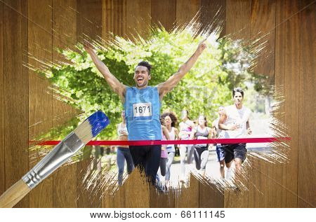 Composite image of racer crossing finishing line with paintbrush dipped in blue against wooden surface with planks