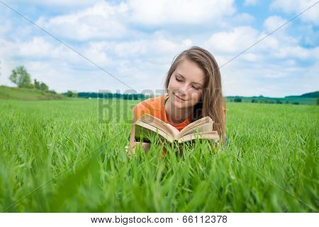 Beautiful young woman - student reading book on grass, against background of summer green park. Clos