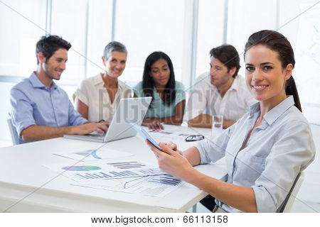 Attractive businesswoman smiling at the camera during a business meeting while using a tablet