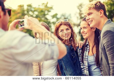 summer holidays, electronics and teenage concept - group of smiling teenagers taking photo with digital camera outside