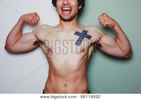 Young Athletic Man With Tattoo Flexing His Muscles