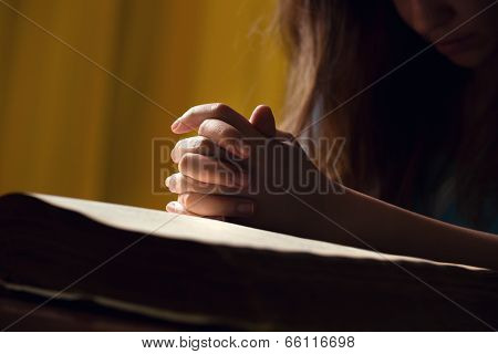 Girl Praying With Hands On Bible