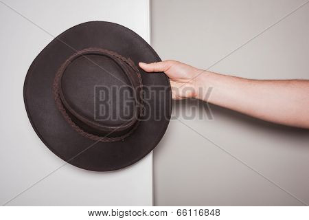 Hand Holding A Cowboy Hat Against Dual Colored Background