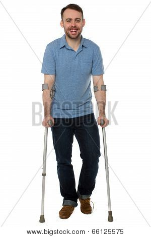 Smiling Young Man Using Crutches