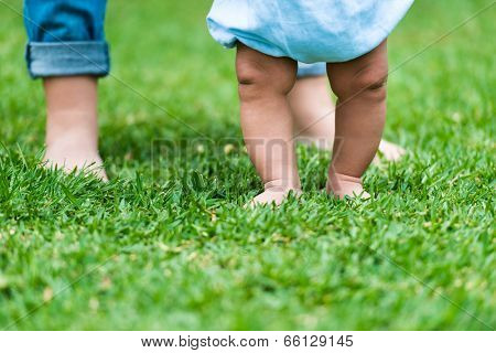 small baby feet on green grass