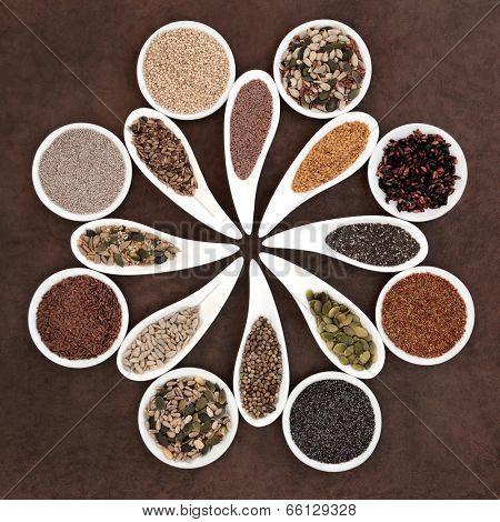 Large seed super food selection in porcelain bowls over brown lokta paper background.