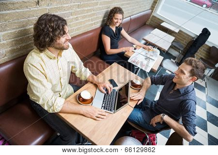 High angle view of male and female customers spending leisure time in cafeteria