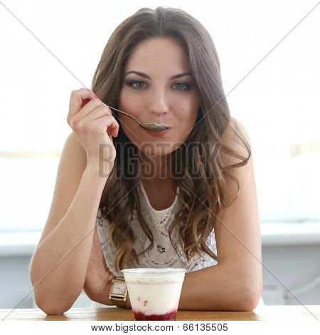 Cute, attractive woman eating yoghurt