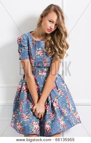 Shy, curly woman in cute dress