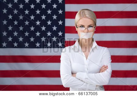 Young girl with her mouth sealed over American flag background