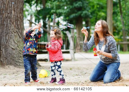 Mother And Two Little Children Playing Together On Playground