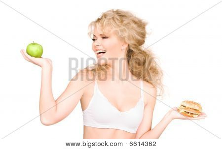 Woman Choosing Between Burger And Apple