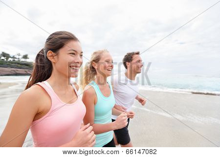 Group running on beach jogging. Exercising runners and friends training outdoors living healthy active lifestyle. Multiracial fitness runner people working out together outside smiling happy.