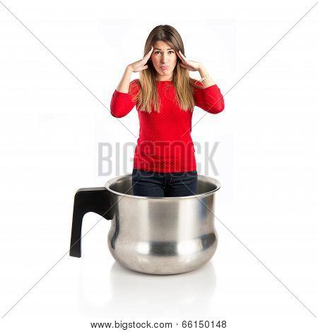 Cute Girl With Headache Inside Saucepan Over White