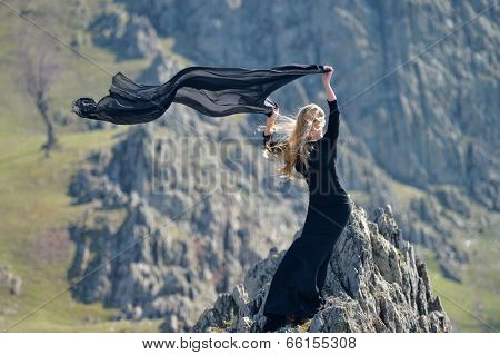 youn woman wearing black dress outdoor on rocks
