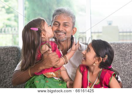 Happy Indian family at home. Asian girl kissing her father, sitting on sofa. Parent and children indoor lifestyle.