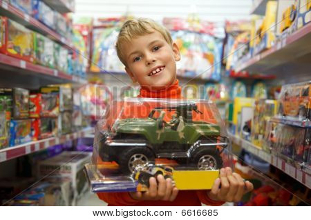 The Boy In Shop With The Toy Machine In Hands