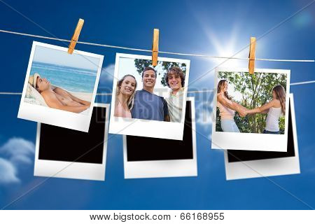Composite image of instant photos hanging on a line against blue sky