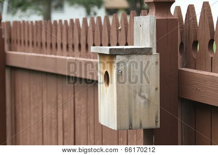 Handmade birdhouse on a picket fence