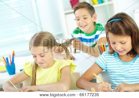 Portrait of lovely schoolgirls drawing at workplace while their schoolmate on background pulling hair of one of them