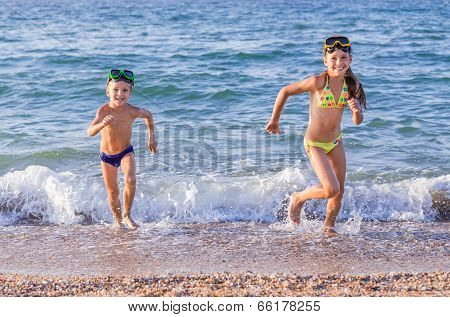 Happy kids runs from the sea