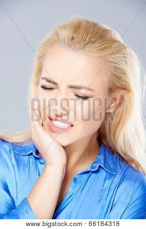 Beautiful young blond woman wincing in pain holding her hand to her jaw and closing her eyes against the throbbing