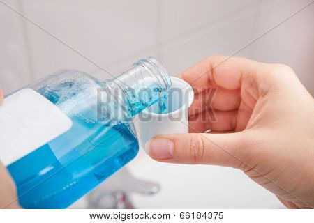 Person Pouring Liquid In Container