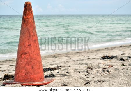 An orange safety cone in the sand.