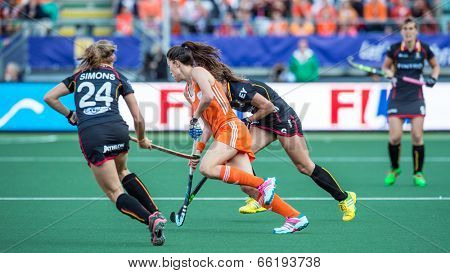 THE HAGUE, NETHERLANDS - JUNE 2: Dutch Star player Naomi van As rushes through two Belgian Defenders during the World Cup Hockey. Netherlands beat Belgium 3-0