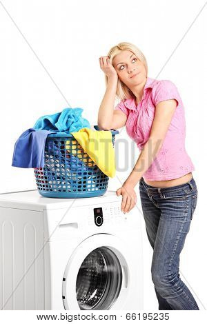 Bored woman standing by a washing machine isolated on white background