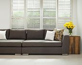 stock photo of louvers  - Grey sofa with pillows infront of lovered windows - JPG
