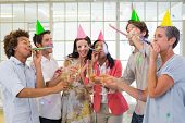 stock photo of office party  - Casual business team celebrating with champagne and party horns in the office - JPG