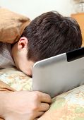 stock photo of weeping  - Sad Teenager Weeps with Tablet Computer in the Bed at the Home - JPG