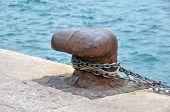 stock photo of bollard  - Old mooring bollard and chain in port Croatia - JPG