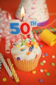 stock photo of 50th  - Delicious cupcake with 50th candle on top with hat - JPG