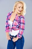 picture of flirtatious  - Sexy seductive young blond woman wearing a trendy knotted checked shirt and jeans laughing as she looks flirtatiously to the side - JPG