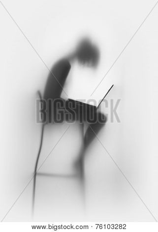Slim woman with laptop computer, sitting on a chair, silhouette