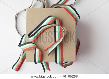 Tangled ribbon in UAE flag colors. A gift box from top view on white background.