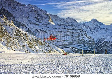 Red Helicopter Flying Near Swiss Ski Resort Near Jungfrau Mountain