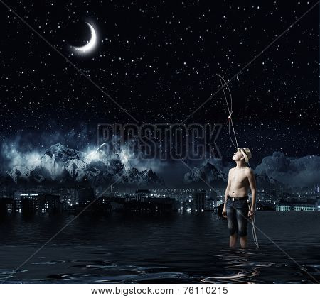Young boy at night with fishing rod