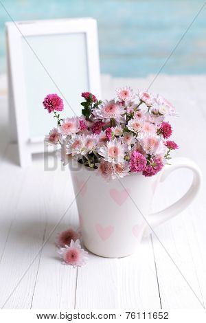 Beautiful flowers in cup on table on light blue background