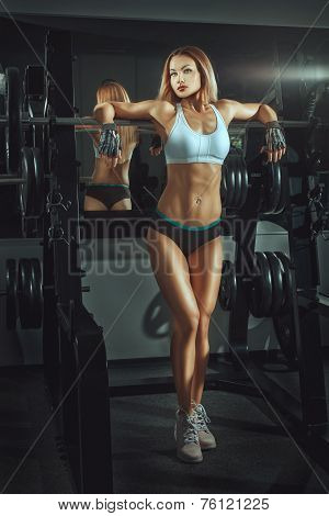 Sporty Girl Standing Near Barbell In Gym.