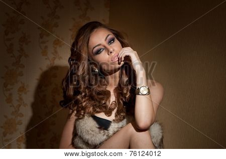 Attractive sexy young woman wrapped in a fur coat sitting in hotel room. Portrait of sensual female