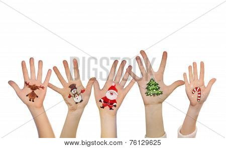 Children's hands raising up with painted Christmas symbols: Santa Claus, Christmas tree, Snow man, r
