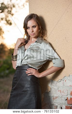 Elegant glamour woman wearing brown skirt and blouse outdoor in the park at sunset. Beautiful woman